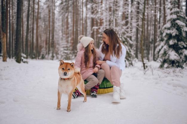 Madre felice e piccola ragazza sveglia in outwear caldo rosa che cammina divertendosi giostre tubo gonfiabile della neve con il cane rosso di shiba inu nella foresta di inverno freddo bianco nevoso all'aperto