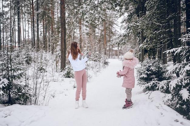 Madre felice e bambina carina in outwear caldo rosa che camminano giocando a palle di neve combattono divertendosi in inverno bianco come la neve