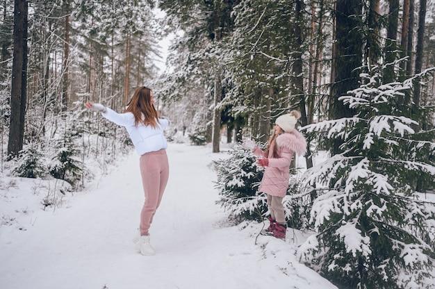 Madre felice e bambina carina in outwear caldo rosa che camminano giocando a palle di neve combattono divertendosi