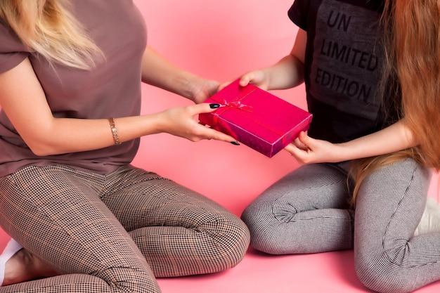 Madre felice e piccola figlia in abiti casual con scatola regalo su sfondo rosa. il concetto celebra la festa della mamma o la festa della donna, trascorrendo del tempo insieme ai bambini e alle relazioni familiari