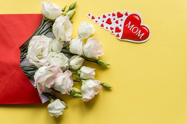 Felice festa della mamma bouquet di fiori bianchi eustoma con cuore rosso su sfondo luminoso fiori di primavera per la festa della mamma.
