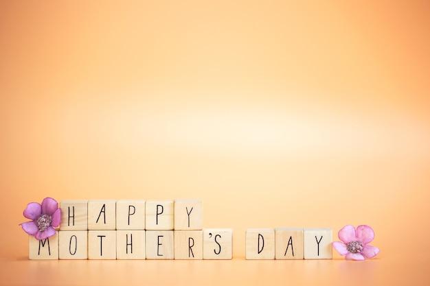 Iscrizione di festa della mamma felice su cubi di legno con fiori primaverili viola