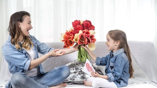 Buona festa della mamma. la piccola dolce figlia con un grande mazzo di tulipani si congratula con sua madre. all'interno del soggiorno, il concetto di una vita familiare felice
