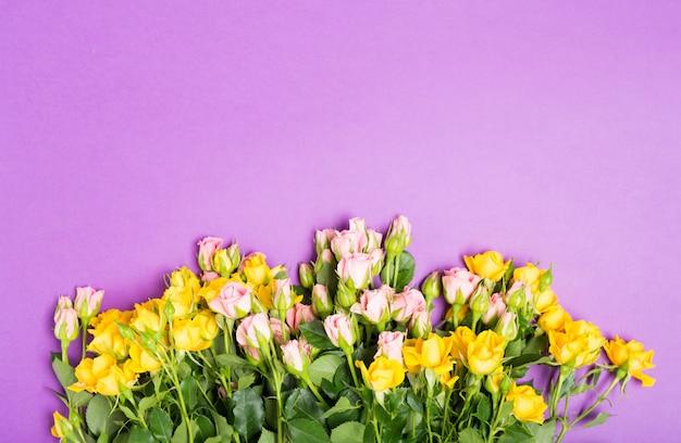 La festa della mamma felice con le rose rosa gialle fiorisce sul fondo porpora della tavola