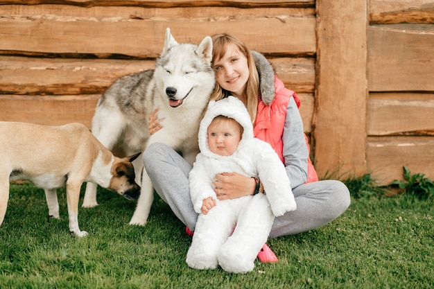 Madre felice che si siede sull'erba e che tiene bambino divertente insieme a due bei cani.