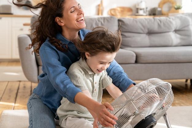 La madre felice e il figlio piccolo si godono il soffio del vento rinfrescante dal ventilatore seduto sul pavimento nel soggiorno