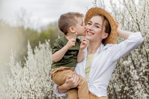 Felice madre e figlio divertirsi insieme. la madre abbraccia delicatamente suo figlio. sullo sfondo sbocciano fiori bianchi. festa della mamma