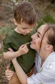 Madre felice e figlio che hanno divertimento insieme. la madre abbraccia dolcemente suo figlio
