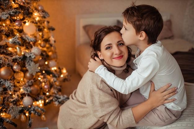 Felice madre e figlio a casa in camera da letto vicino all'albero di natale