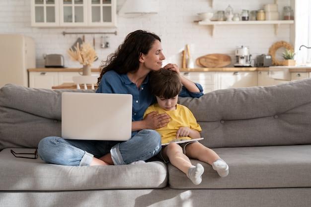 Madre felice donna d'affari di successo che si lega al figlio in età prescolare su covid felice di lavorare a distanza