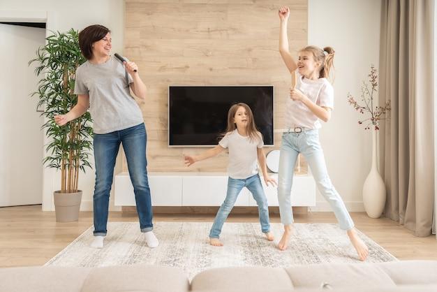 Madre felice e due figlie divertendosi cantando la canzone del karaoke con le spazzole per capelli.