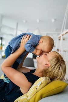 Madre felice con un bambino adorabile a casa. famiglia, bambino, concetto di amore.