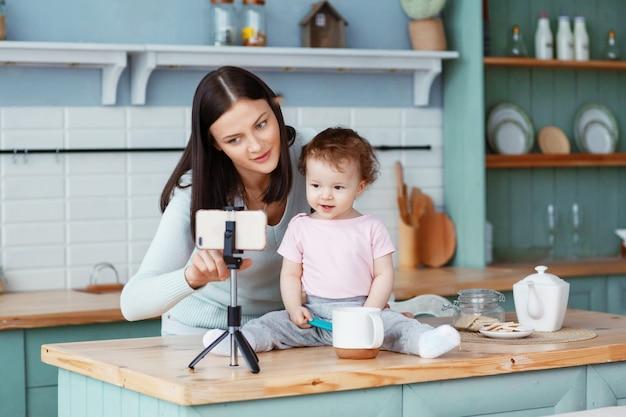 Una madre felice con un bambino si siede in cucina al tavolo e scrive video per il blog su uno smartphone collegato a un treppiede