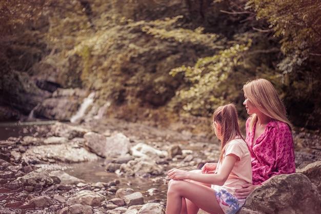 Madre felice con un bambino seduto sull'erba su uno sfondo di montagne boscose