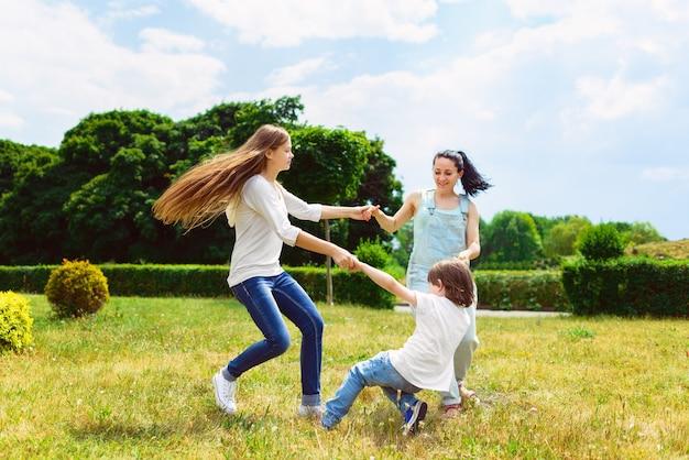 Felice madre con figlia e figlio in esecuzione sull'erba sorridendo.
