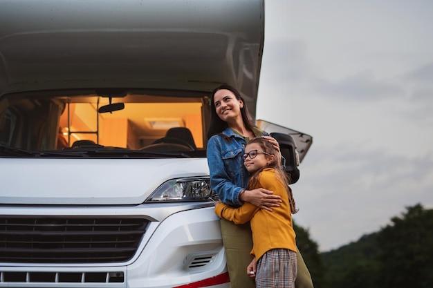 Felice madre con la figlia in piedi in macchina all'aperto in campeggio al tramonto caravan vacanza in famiglia viaggio