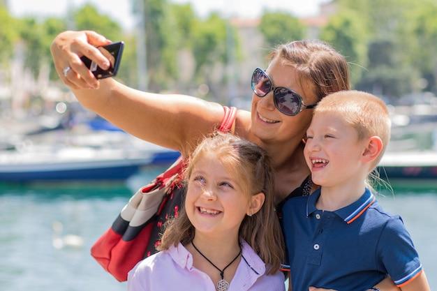 Madre felice con i suoi figli stanno prendendo un selfie in una giornata di sole