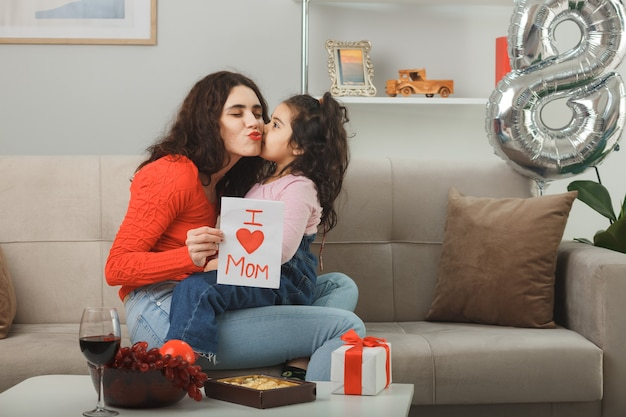 Felice madre con la sua piccola figlia seduta su un divano con in mano un biglietto di auguri sorridente allegramente in un luminoso soggiorno che celebra la giornata internazionale della donna l'8 marzo
