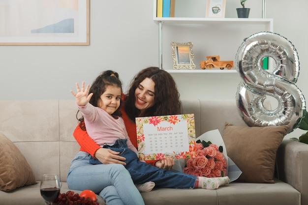 Madre felice con la figlia piccola seduta su un divano con un mazzo di fiori e il calendario del mese di marzo sorridendo allegramente nel soggiorno luminoso che celebra la giornata internazionale della donna l'8 marzo