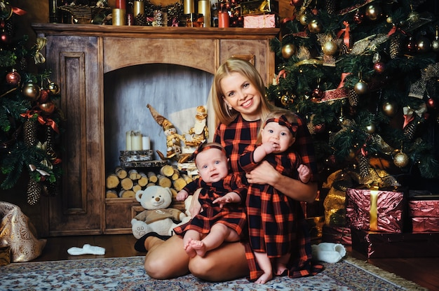 Una madre felice con i suoi figli gemelli nell'interno della casa di capodanno sullo sfondo di un albero di natale.