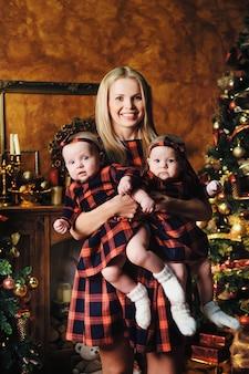 Una madre felice con i suoi figli gemelli nell'interno della casa di capodanno sullo sfondo di un albero di natale