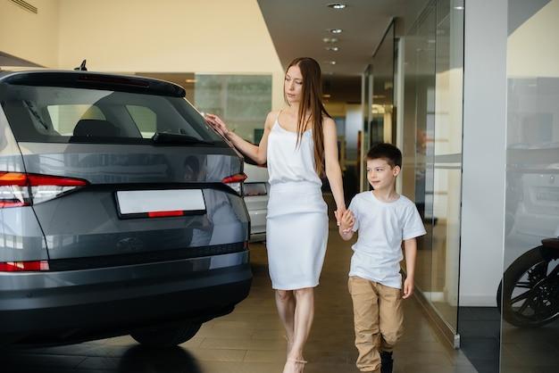 Una madre felice con il suo giovane figlio sceglie una nuova auto in una concessionaria di automobili. acquisto di un'auto.