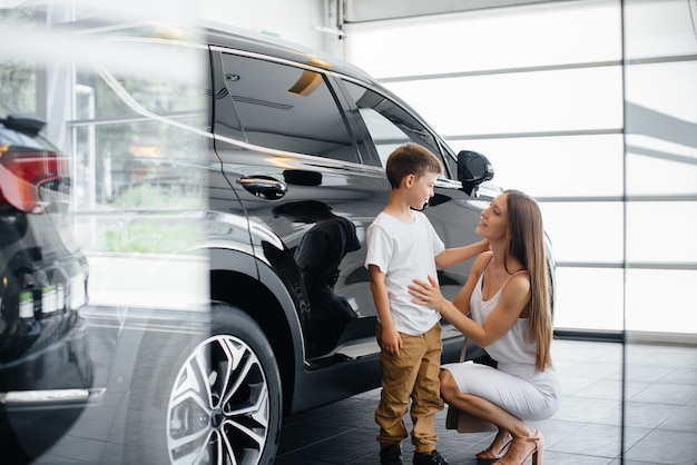 Una madre felice con il suo giovane figlio sceglie una nuova auto in una concessionaria di automobili