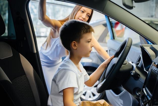 Felice madre con il suo giovane figlio sceglie una nuova auto presso una concessionaria di automobili