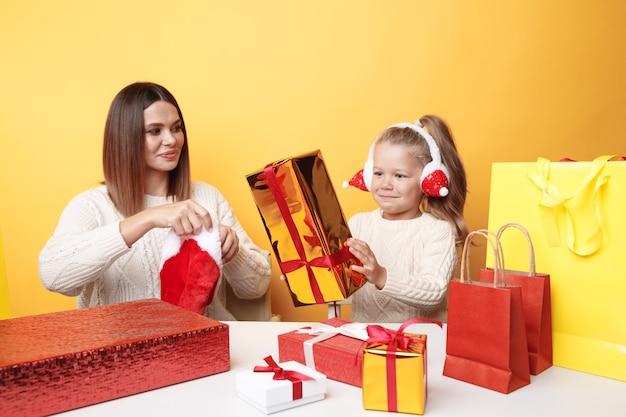Madre felice con il bambino che si diverte insieme seduti alla scrivania con regali