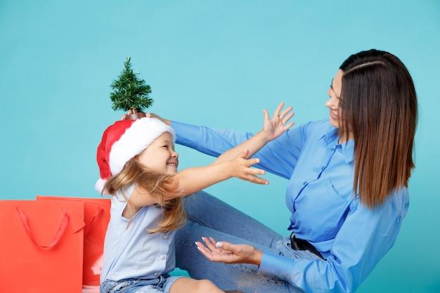 Madre felice con la piccola figlia con regali isolati sopra la parete blu dello studio