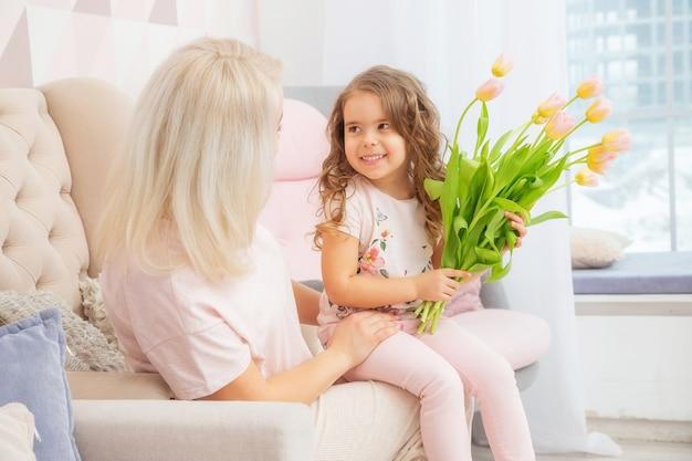 Buona festa della mamma. la figlia del bambino si congratula con la mamma e le dà il mazzo di fiori tulipani nel soggiorno rosa nella loro casa.