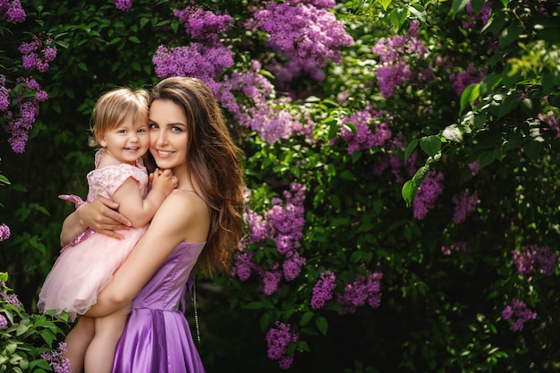Buona festa della mamma! copia spazio. la bella giovane donna e la sua piccola figlia affascinante stanno abbracciando e sorridendo. alberi fioriti