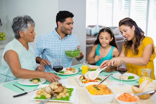 Famiglia felice della multi generazione che ha pasto sulla tavola