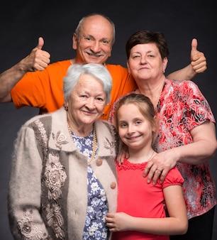 Felice famiglia di diverse generazioni in posa in studio su un muro grigio