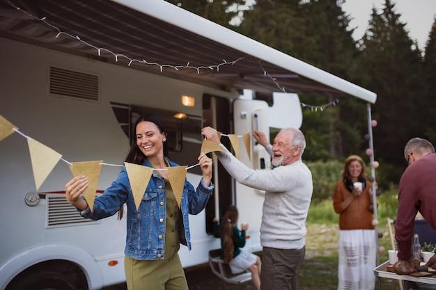 Felice famiglia multigenerazionale che prepara una festa in auto all'aperto in campeggio, viaggio di vacanza in roulotte.