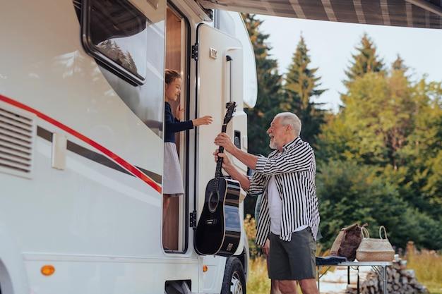 Felice famiglia multigenerazionale che disimballa e parla in auto, viaggio di vacanza in roulotte.