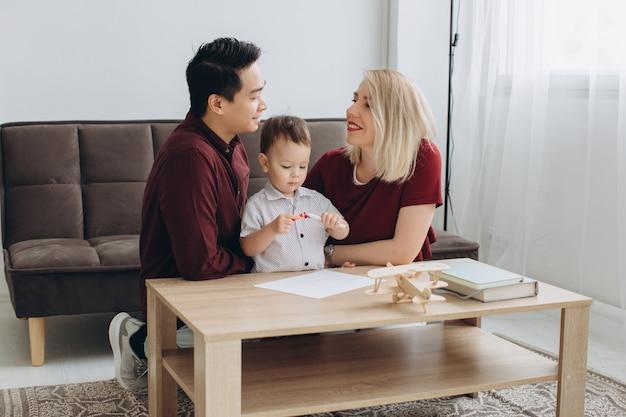 Famiglia multiculturale felice. uomo asiatico e disegno caucasico della donna con il loro figlio.
