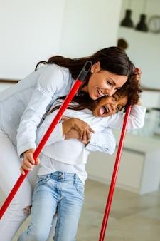 Felice famiglia multietnica che pulisce casa e si diverte. i bambini aiutano la madre a riordinare l'appartamento.