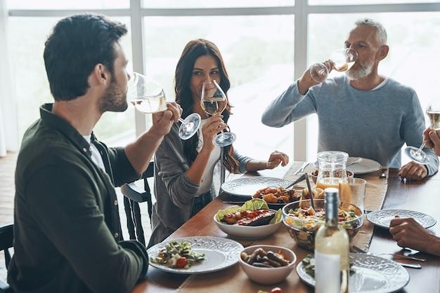 Felice famiglia multigenerazionale che beve vino mentre si cena insieme