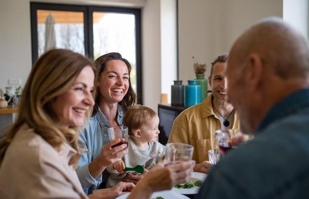 Una famiglia multigenerazionale felice in casa a mangiare un pranzo sano, divertendosi.