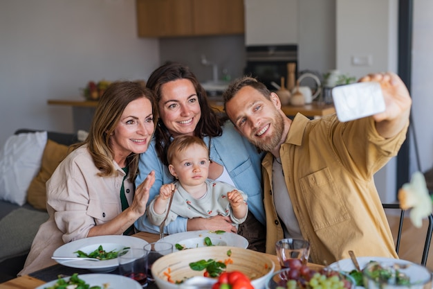 Felice famiglia multigenerazionale al chiuso a casa che mangia un pranzo sano, facendo selfie con lo smartphone.