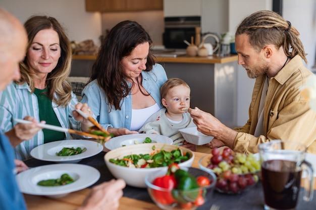 Una famiglia multigenerazionale felice al chiuso a casa che mangia un pranzo sano.