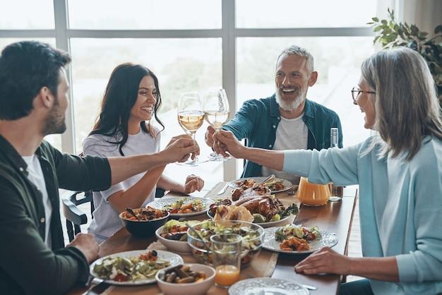Felice famiglia multigenerazionale che si brinda a vicenda e sorride mentre cena insieme