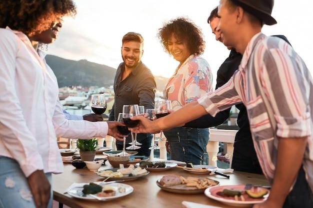 Felici amici multirazziali che cenano e fanno il tifo con il vino all'aperto a casa