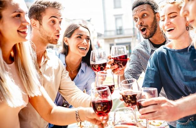 Felici amici multirazziali che si divertono a bere e brindare vino rosso a pranzo