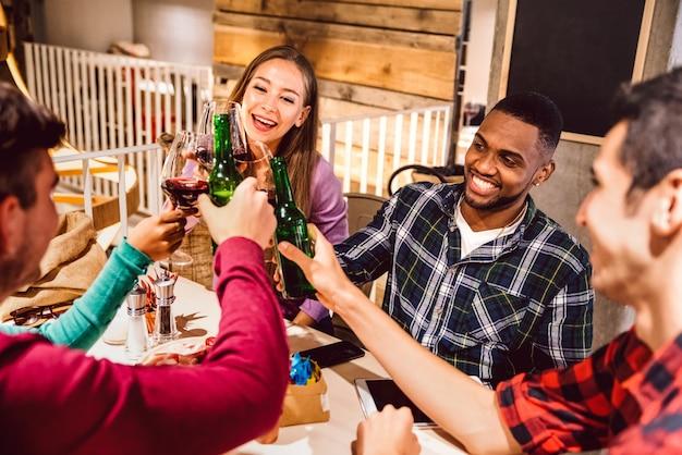 Amici multirazziali felici che tostano birra al coperto al pub birreria