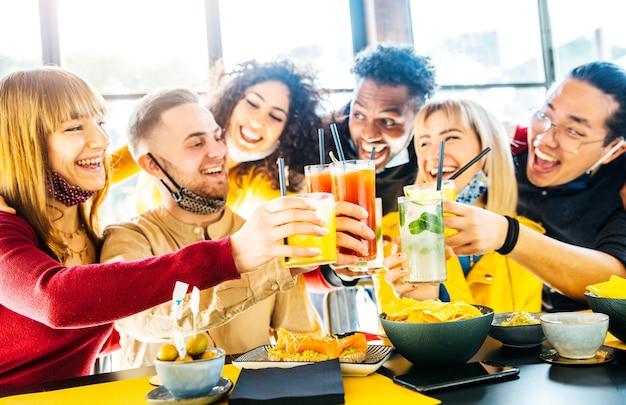 Felici amici multirazziali che indossano maschere per il viso che tostano cocktail al bar ristorante