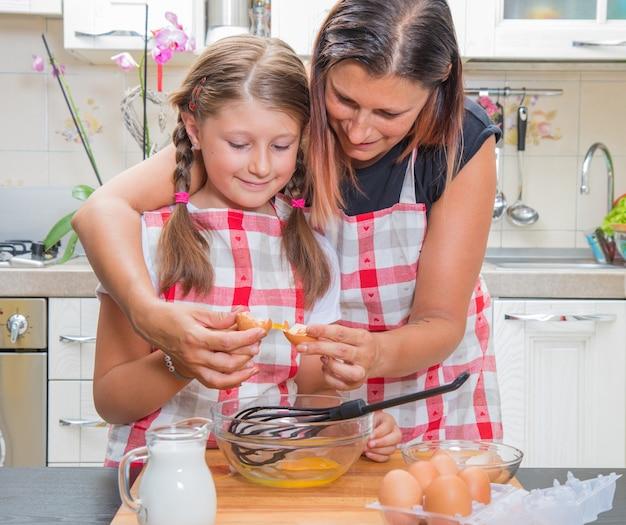 Mamma e figlia felici stanno preparando una torta insieme