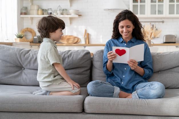 La mamma felice si diverte a leggere la cartolina regalo del figlio piccolo il giorno del compleanno della festa della mamma o di san valentino