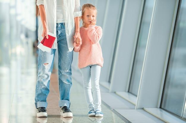 La mamma e la bambina felici con l'imbarco passano all'aeroporto